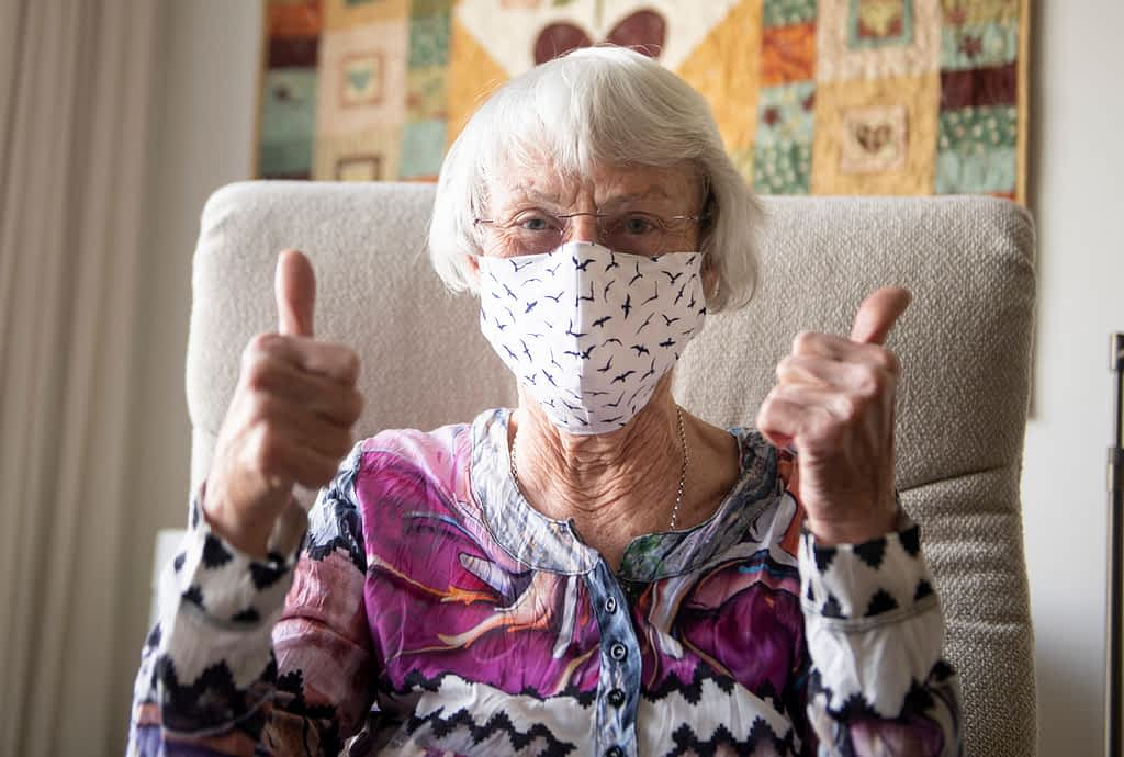 Senior woman with a fitted textile homemade mask, that can feature a filter made of paper towel or a HEPA filter.